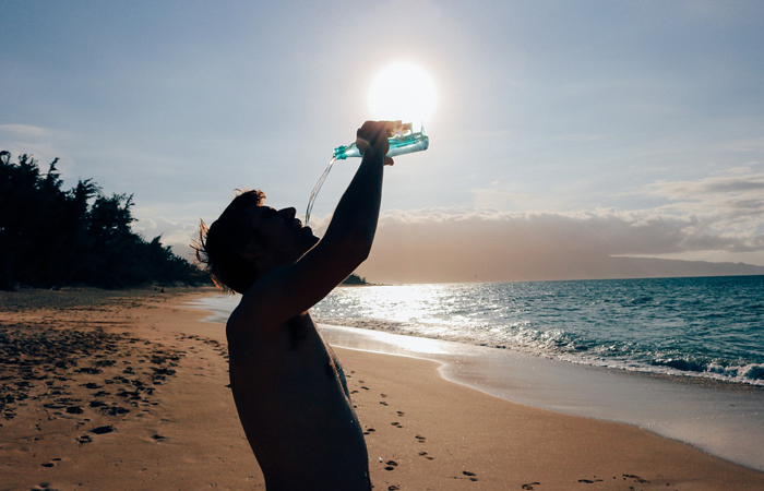 man drinking water under the heat of the sun