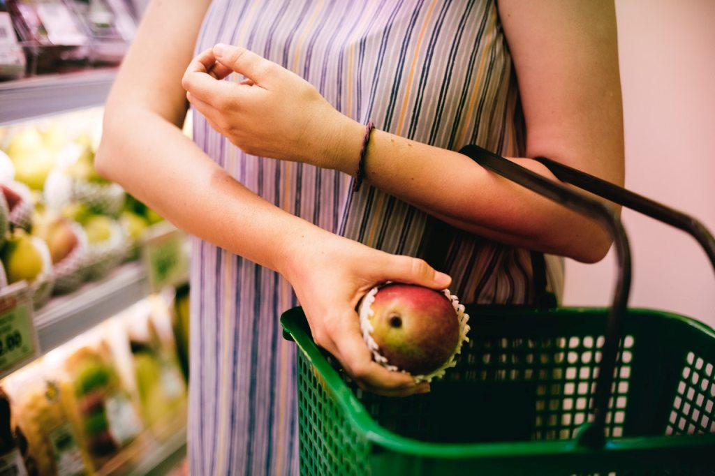 Woman putting red apple in a grocery basket