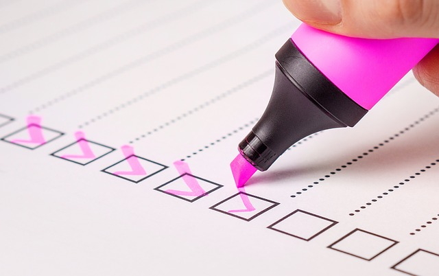 person using pink marker for checklist