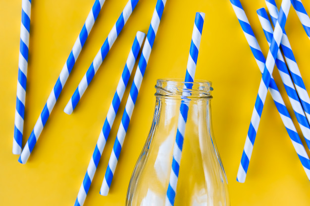 glass bottle and colored stripes paper straws