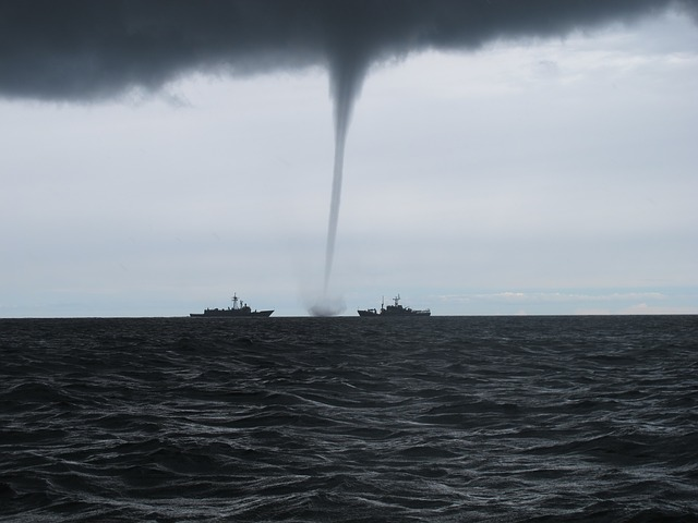 tornado in the sea near two boat